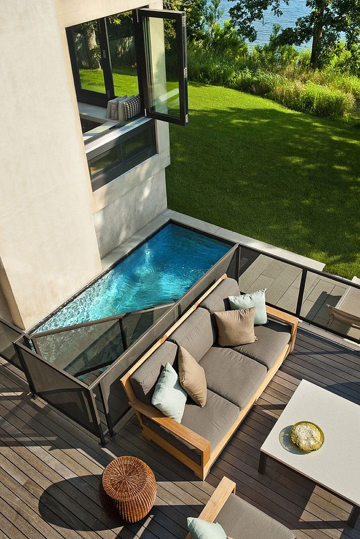 modern small pool, with a metal divide, surrounded by wooden planks, in a garden, containing a sofa and a table, cool backyards, house with an open window nearby