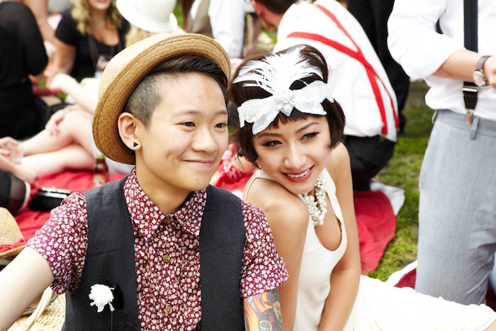 happy-looking couple, sitting next to each other, wearing a short-sleeved patterned shirt, and a black vest, and a white retro gown, straw hat and feathered headband