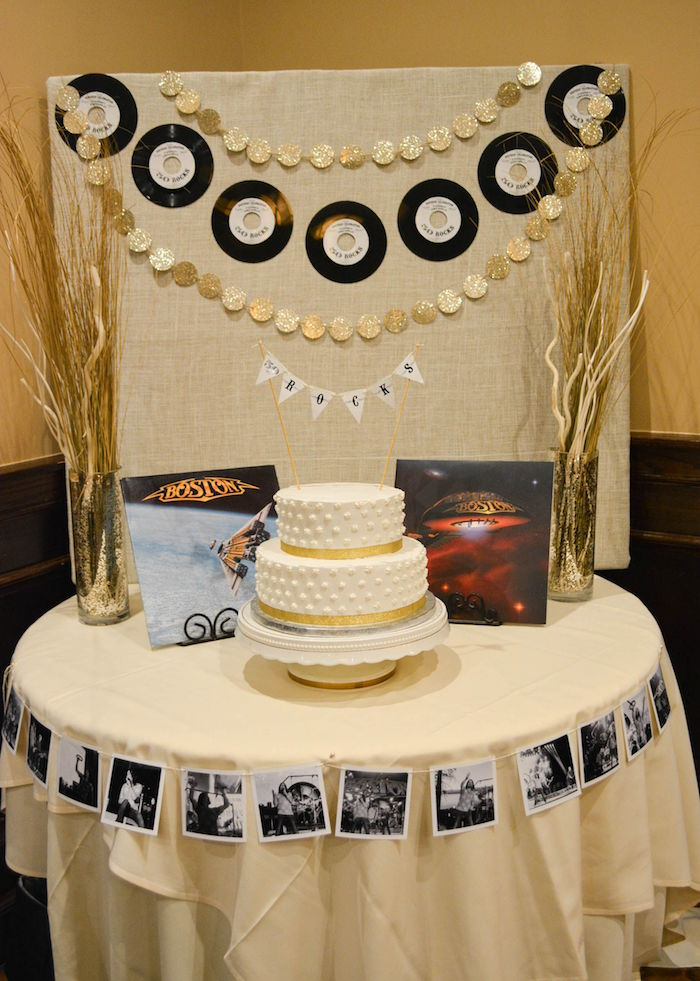 dried plants arranged in two sparkling vases, placed on either side of a white cake, with gold details, vinyl records and two boston albums, 60th birthday color, on a table decorated with black and white photos