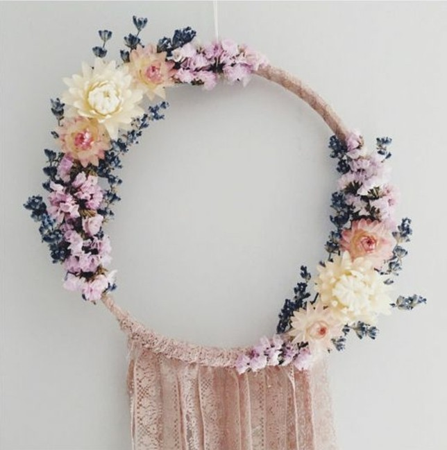 large dream catcher, decorated with pale pink lace ribbons, and flowers in light cream and pink