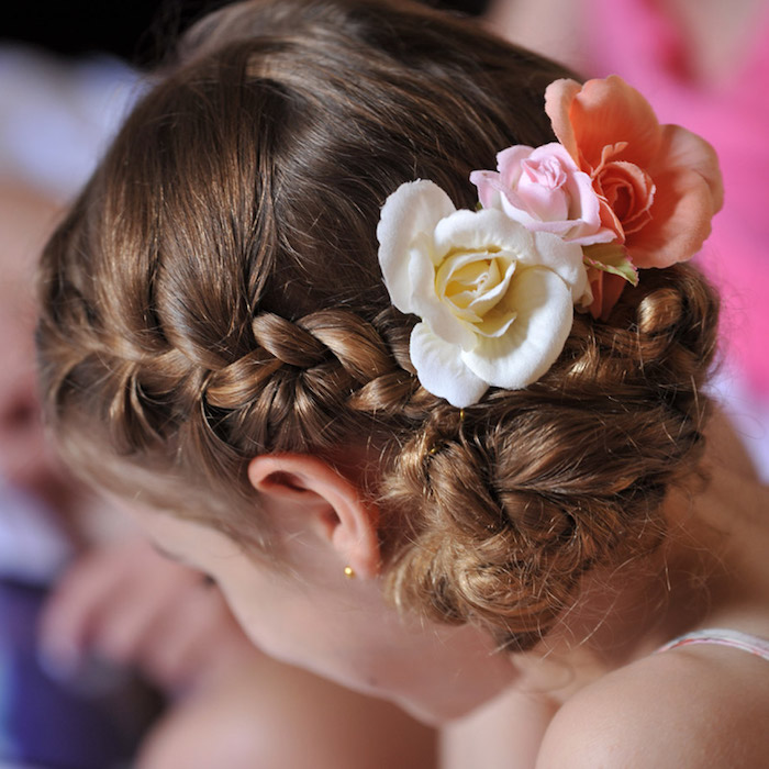 braided brunette hair, decorated with three roses in different colors, cream and pale pink, and pastel orange, on the head of a child, hairstyles for little girls, seen in close up