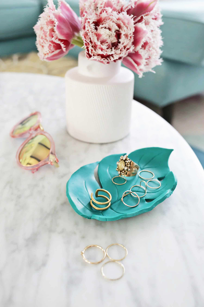 white vase with flowers, leaf shaped turquoise clay jewelry holder, diy gift ideas, placed on marble surface, gold rings inside