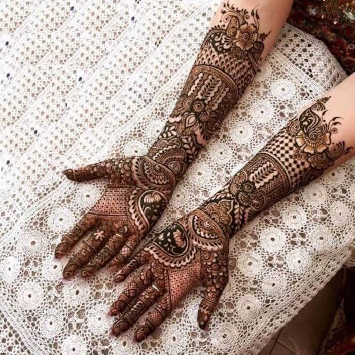 tablecloth made of crochet lace, under a pair of arms, densely decorated with dark brown mehndi, covering the palms and forearms