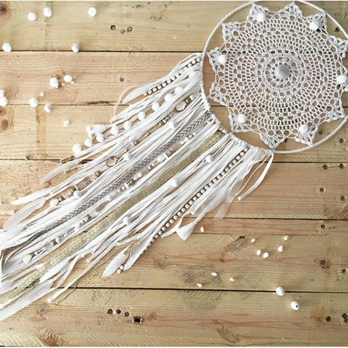 beads in white, a crochet off-white doily, and many ribbons in cream and white, boho dreamcatcher designs, pale wooden floor