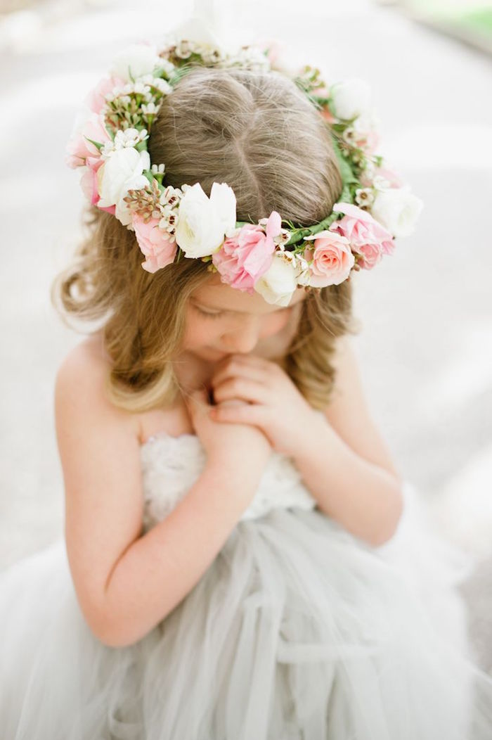 wreath made of white, and pale pink flowers, on the head of a child, with medium long, dark blonde hair, hairstyles for little girls, wearing an off-white tulle dress