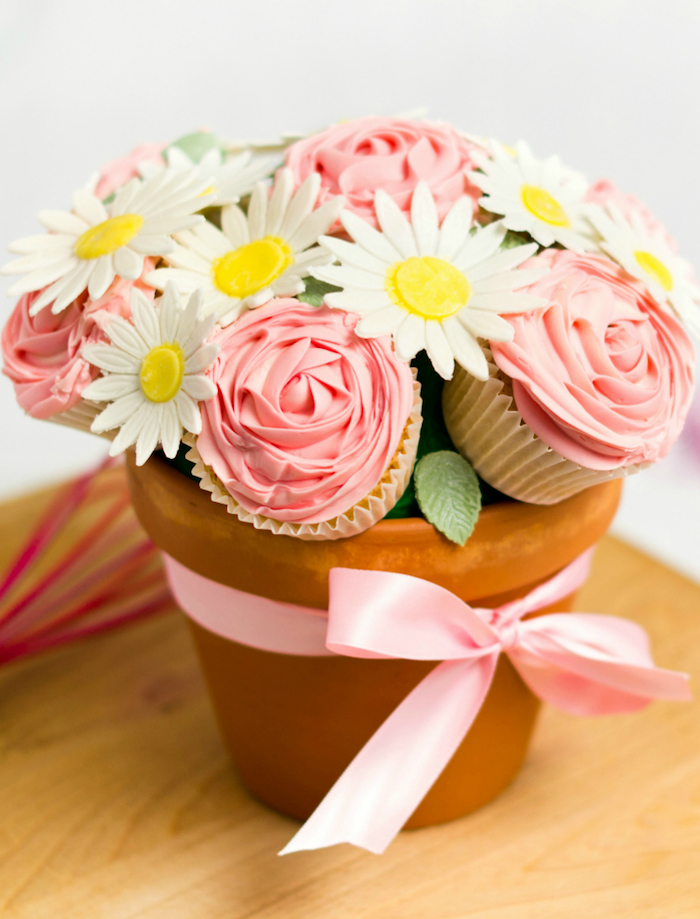 cupcakes and faux sunflowers in ceramic pot, creative diy christmas gifts, pink satin ribbon around, placed on wooden table