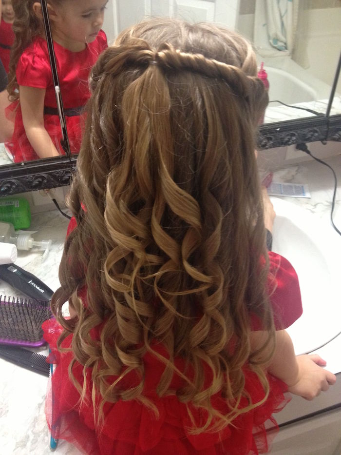 ringlet-like curls, on a long brunette hair, with joined side twists at the top, worn by a small girl, in a fancy red dress