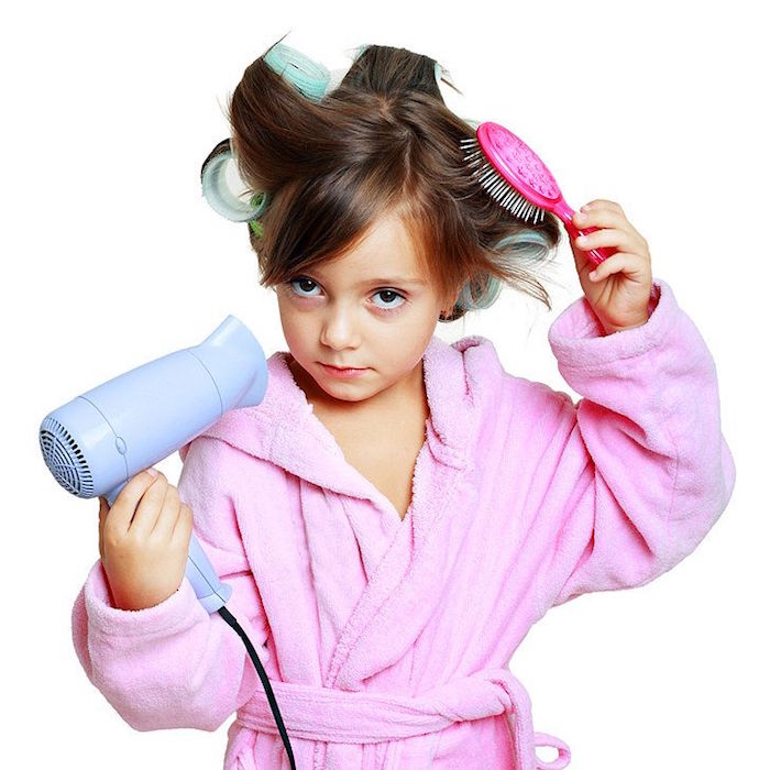 child in a pink bathrobe, with big curlers on her head, cute hairstyles, brushing her hair, with a small pink brush, while holding a blue hairdryer