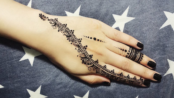 black ring-like motifs, dots and a long, curved detail, running from the wrist, to the index finger, finger henna tattoo ideas