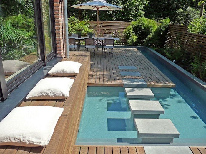 modern patio pool, near a house, bench with three cushions, small backyard pool ideas, garden table with an umbrella, and several chairs