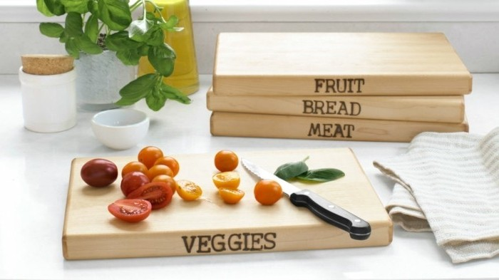 wooden cutting boards, decorated with customized inscriptions, last minute birthday gifts, cherry tomatoes and basil leaves, near a small knife, on one of the boards