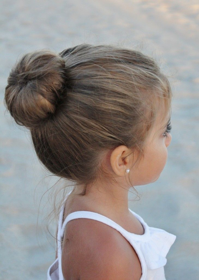 ballerina hair bun, on the head of a small brunette child, cute hairstyles, wearing a white frilly top