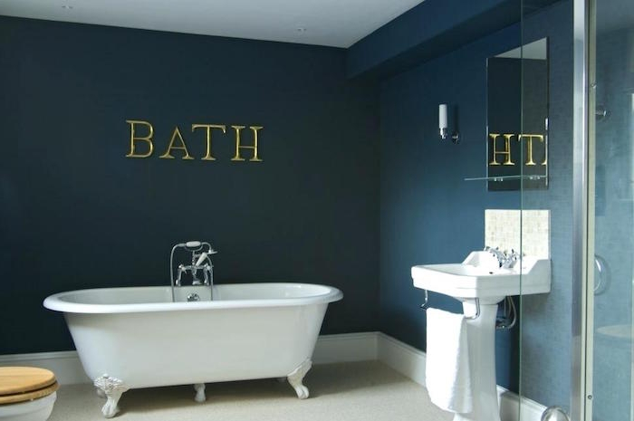 the word bath, spelled in large gold letters, on a dark ocean blue wall, diy bathroom decor, white claw-footed bathtub, and matching white sink