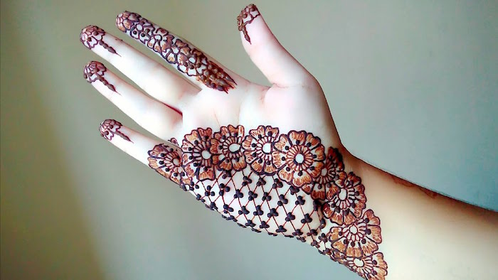 mesh-like henna design, with large detailed flowers, cute henna designs, on the palm and fingertips, of an outstretched hand