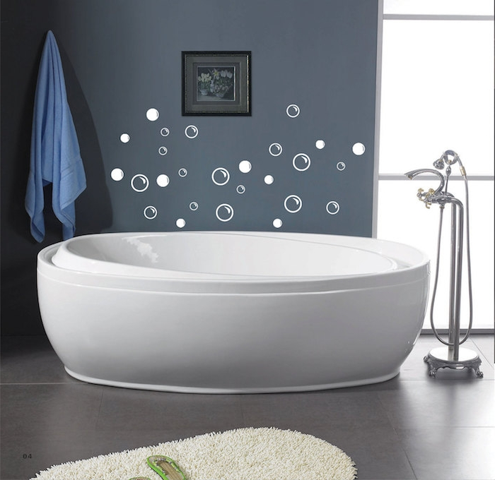 stickers in white, shaped like bubbles, on a dark grey wall, near a modern, white oval bathtub, bathroom decorating ideas on a budget, fluffy cream rug, pale blue towel
