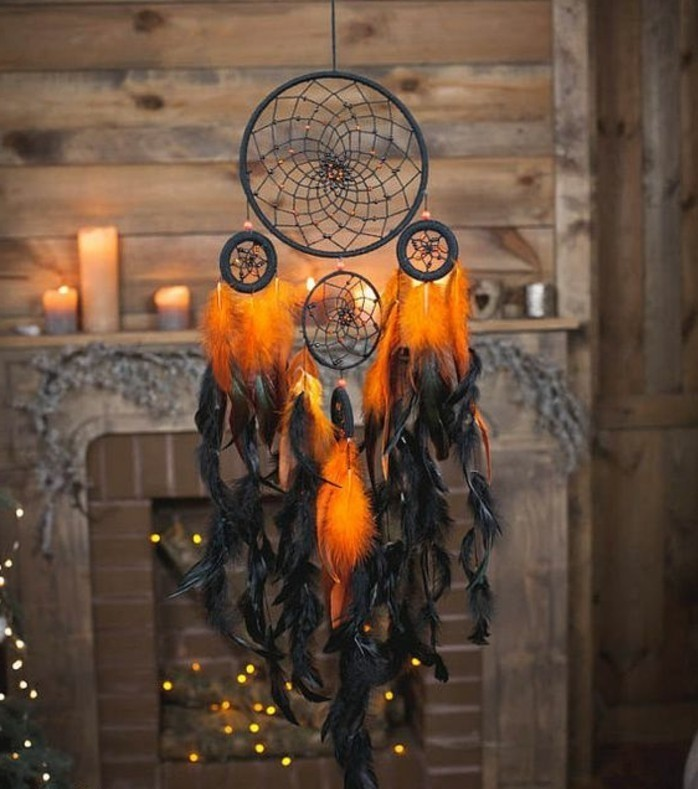 orange and black feathers, hanging from a black dream catcher, with four nets, how to make a dreamcatcher, fireplace with lit candles on the mantelpiece