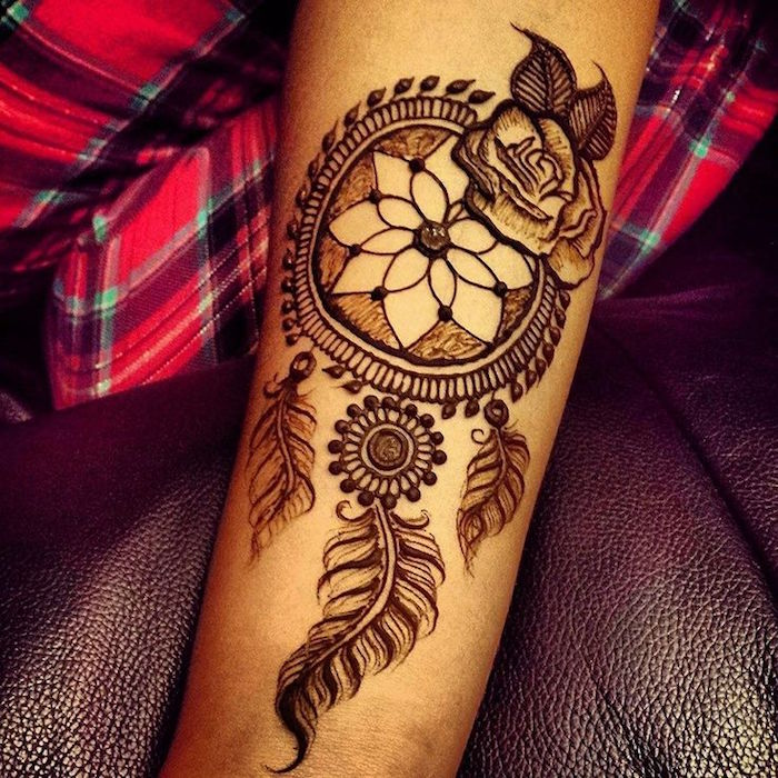 three feathers and a rose, attached to a dreamcatcher, drawn with brown henna, on a person's forearm