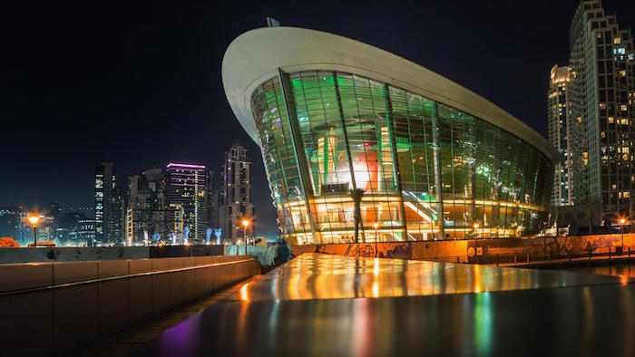 boat-shaped structure, made of glass and metal beams, with an oval white roof, dubai opera house, lit from within, post modernity