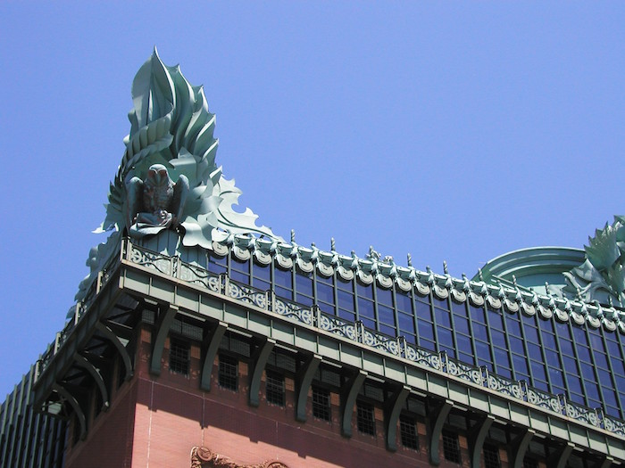 roof detail of the harold washington library, seen in close up, and featuring a bird and a flame-like ornament, postmodernism characteristics