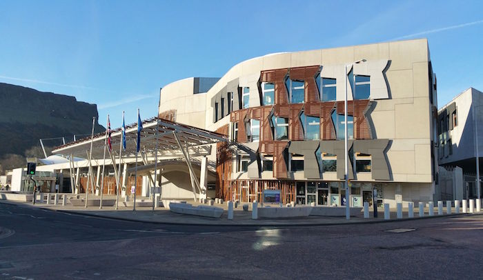 symmetrical building in cream, with brown and grey, and off-white details, postmodern design, scottish parliament building