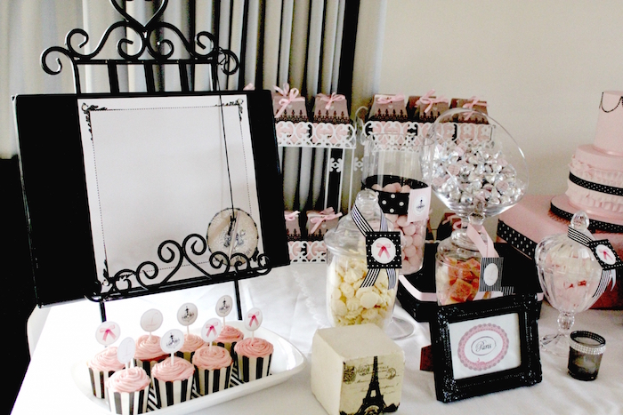 french-themed birthday party, in black and pale pink, table with candies and cupcakes, decorated with an eiffel tower ornament, and other items