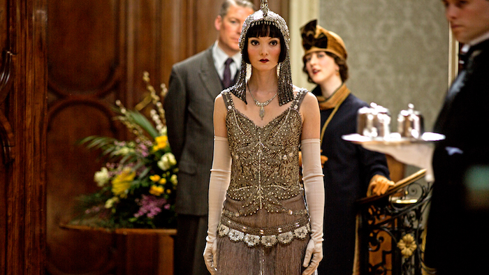 headdress in shimmering silver, on a woman with short black hair, and bold make up, wearing a beige and gold flapper gatsby dress, with pearls and beads