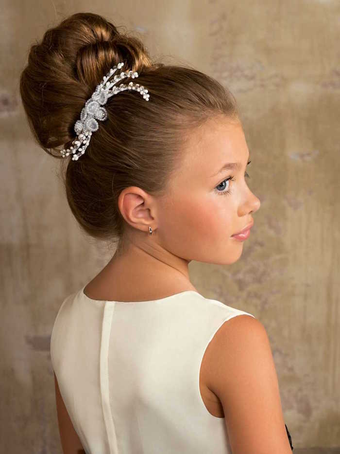 silver hair ornament, with diamante details, decorating the hair bun, of a brunette young girl, wearing a smart white dress