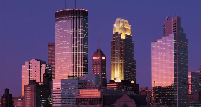 minneapolis at dusk, skyscrapers and other buildings, bathed in pink and purple light, postmodern design, one building lit in yellow