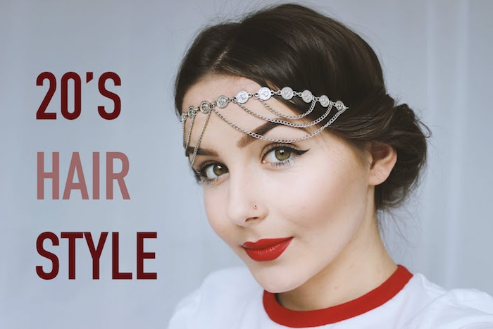 nose stud and eyeliner, bright red lipstick and a silver flapper-style headband, worn by a young woman, in a white and red top