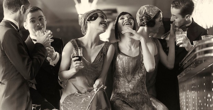 mock-antique black and white photo, featuring laughing and talking young people, dressed in roaring 20s dress, and holding glasses