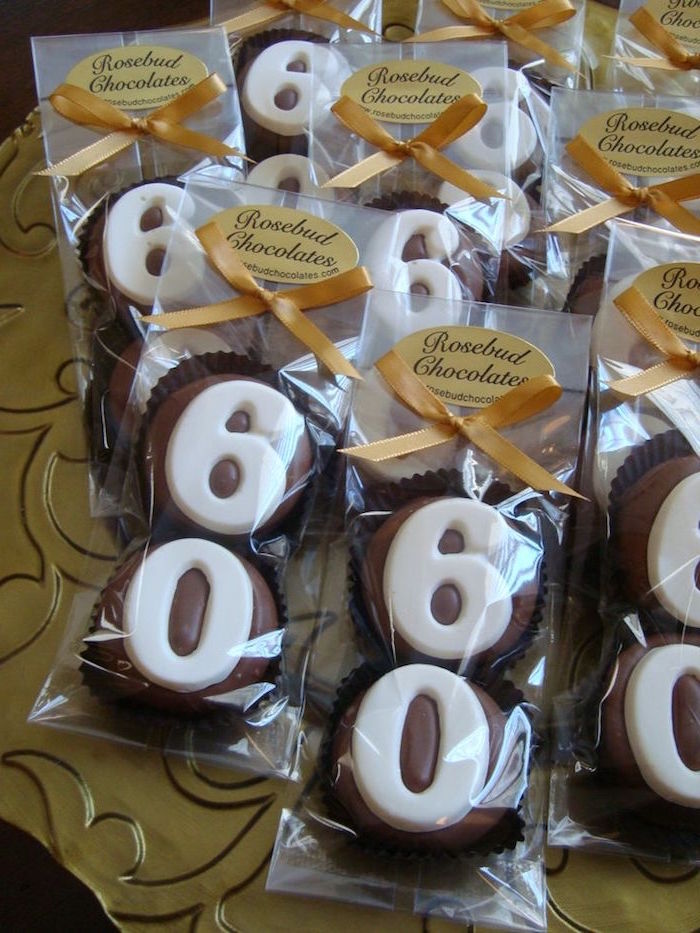 yellow ribbons decorating several clear packages, containing two milk chocolate cupcakes each, decorated with the numbers 6 and 0, made from white chocolate