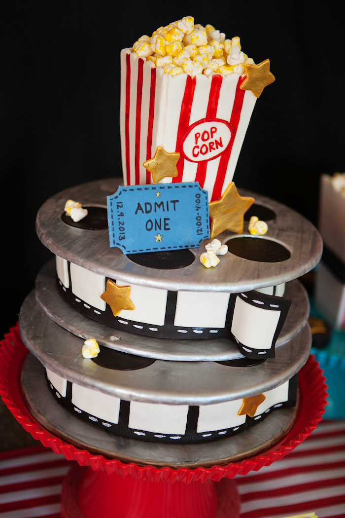 60th birthday decorations, colorful fondant-covered cake, shaped like film reels, and a vintage box of popcorn, decorated with gold stars, and a blue admission ticket