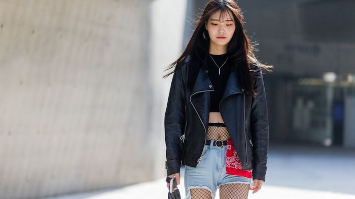 biker leather jacket in black, worn over a black cropped top, 90s clothes womens, girl in denim shorts, and fishnet tights