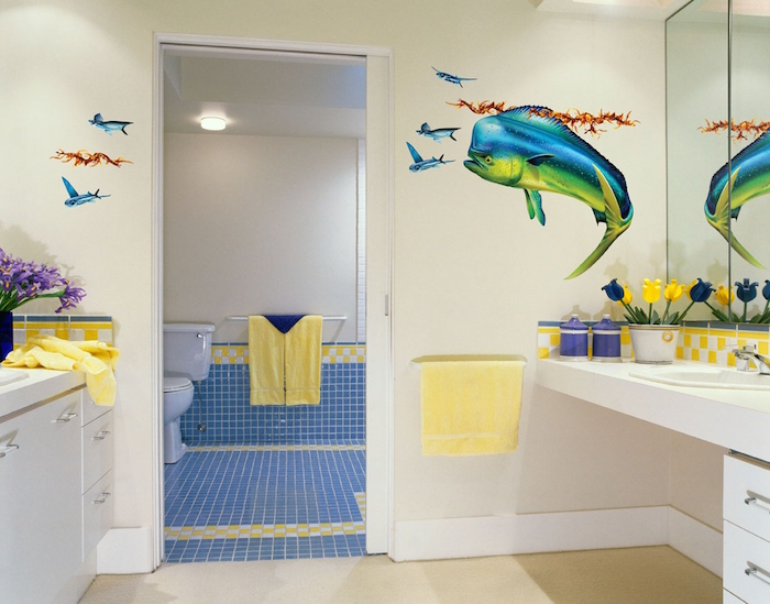 one big and several small fish decal stickers, on the pale yellow wall, of a room containing white cupboards, floral decorations and yellow towels, modern bathroom ideas, open door revealing a toilet in the next room