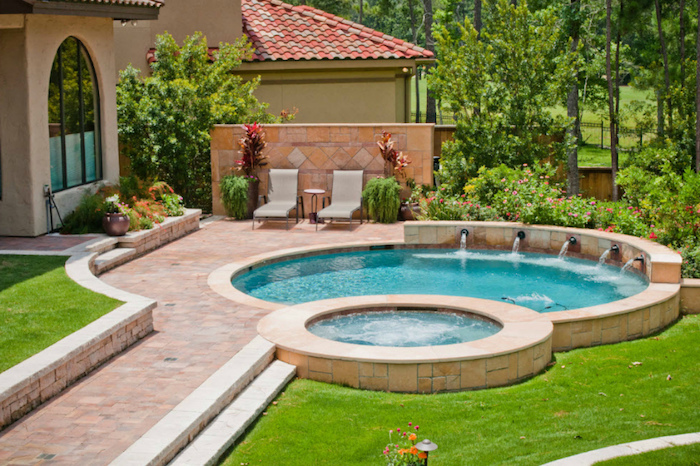 set of two pools, with five faucets, pouring water into the bigger one, green grass and a tiled path, backyards with pools, lots of green trees and a house