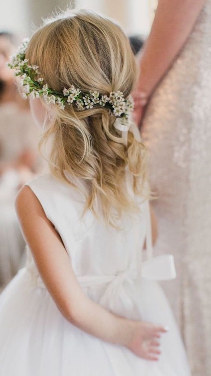 straw blonde shoulder-length hair, with loose curls, worn by a young child, in a white flower-girl dress, girl haircuts, flower wreath wth small white blossoms