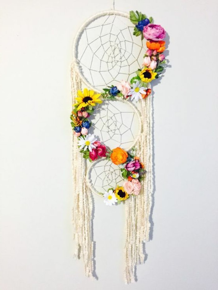 variety of flowers in different colors, decorating a white dream catcher, with tree nets, and long off-white tassels