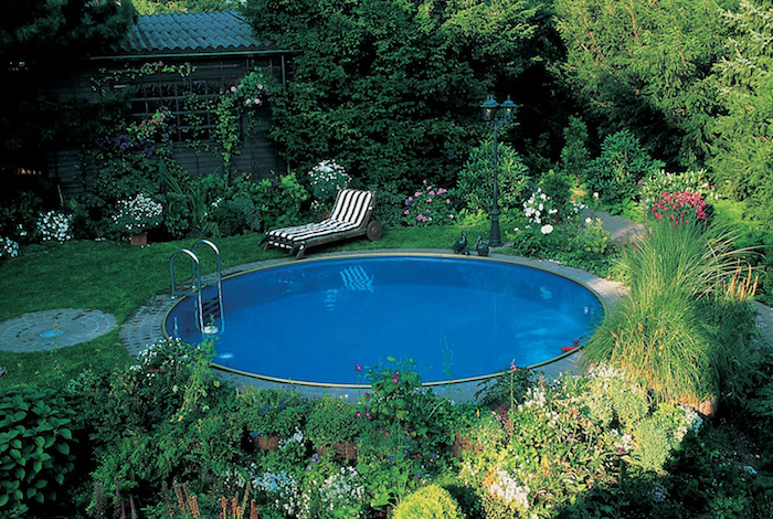 trees and shrubs, flowers and grass, in a green garden, containing a blue circular pool, striped sun bed nearby