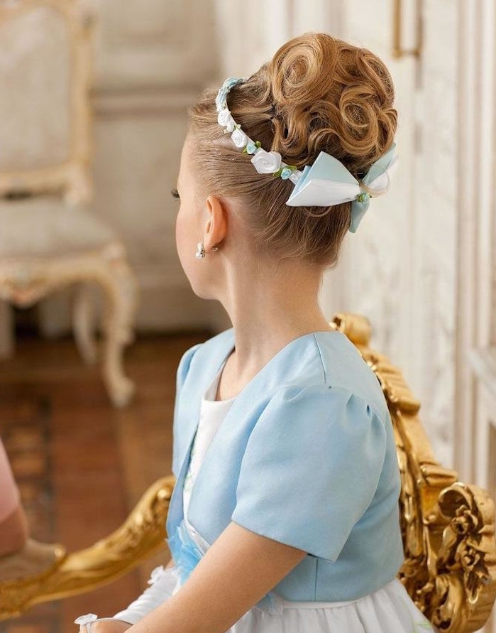 duck's egg blue short blazer, worn over a white dress, by a girl with curly up-do, decorated with a pale blue and white bow