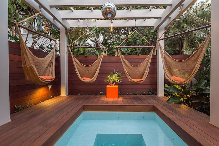 disco ball and four hammock swings, hanging from a white wooden structure, built over a small rectangular pool