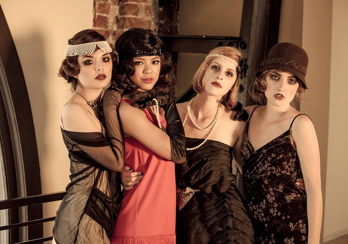 women dressed in 1920s costumes, dresses in white, coral pink and black, great gatsby outfits, long pearl necklace, vintage headbands and a cloche hat
