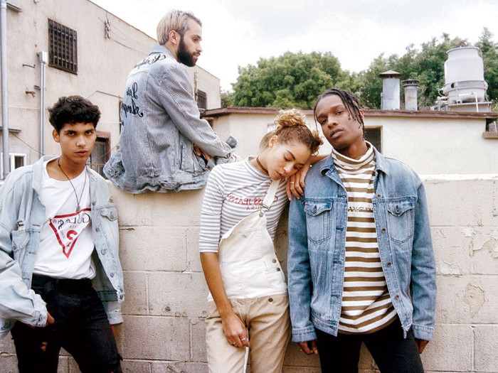 group of young people, dressed in 90s getup, oversized denim jackets, overalls and a turtleneck
