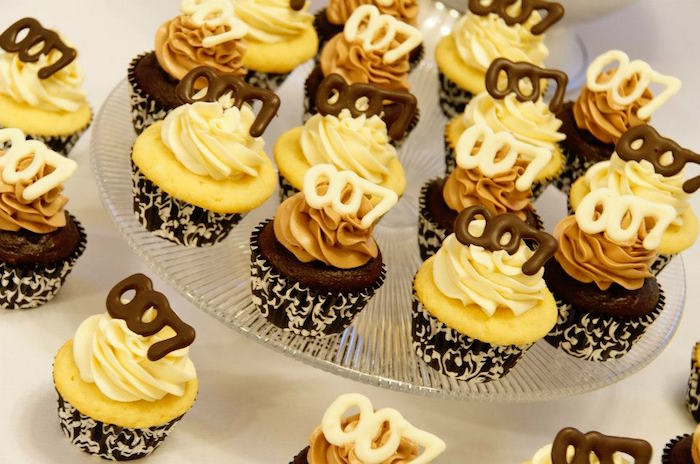 vanilla and chocolate cupcakes, in black and white wrappers, with cream and beige frosting, and white and dark chocolate toppers, shaped like the number 007