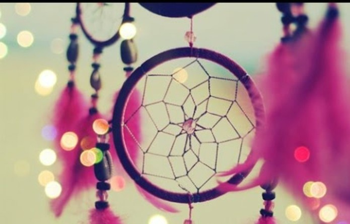 bokeh effects on an image, showing a close up, of a purple dream catcher, surrounded by hot pink feathers and beads