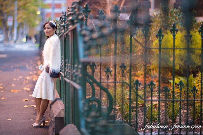 fluffy white fur coat, worn over a white silky midi dress, by a brunette woman, with a small white hat, and nude colored pumps, leaning on a green, decorative metal fence