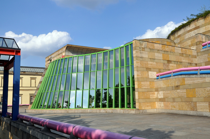 bright green window frames, and reflective glass panels, on a building covered in beige and cream tiles, modernism and postmodernism, pink and blue pipes