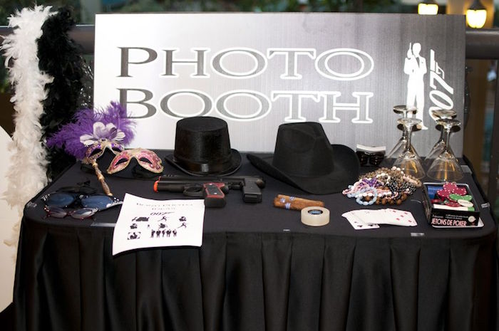 masks with feathers, sunglasses and hats, toy guns and cigars, cocktail glasses and other items, on a 1920s gangster-themed photo booth
