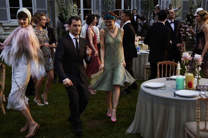 dancing people dressed in roaring 20s fashion, on a green lawn near a house, set table in one corner, woman in a green, embroidered flapper dress, man in a smocking