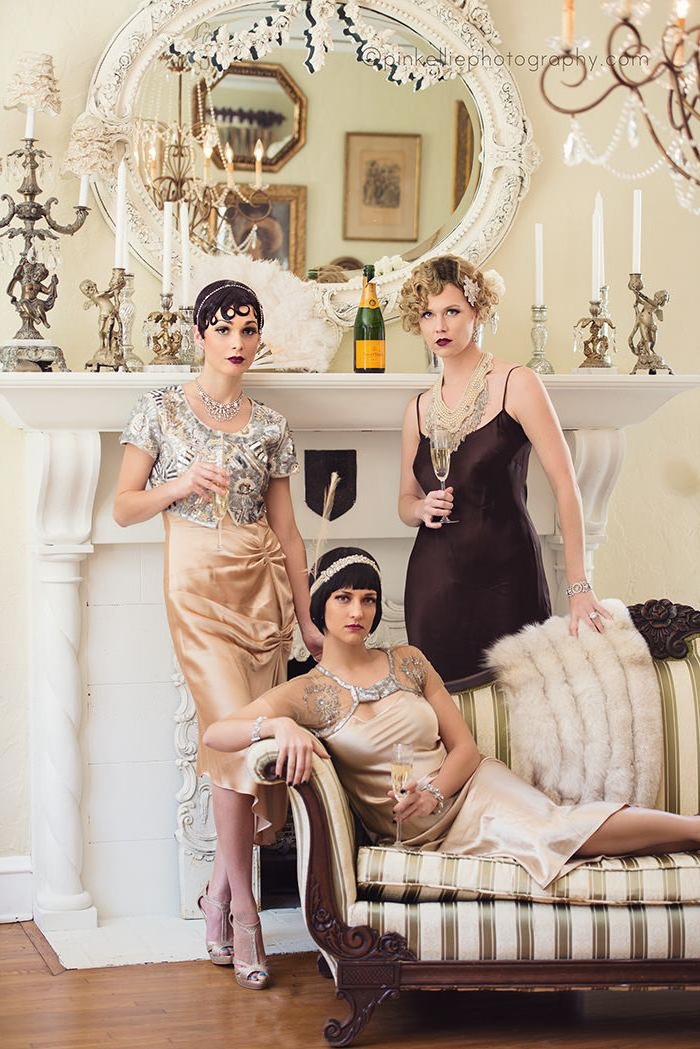 champagne flutes in the hands of three women, each dressed in a gatsby themed dress, pale peach silk with silver embroidery, black satin slip-style gown, in a room with classical decor