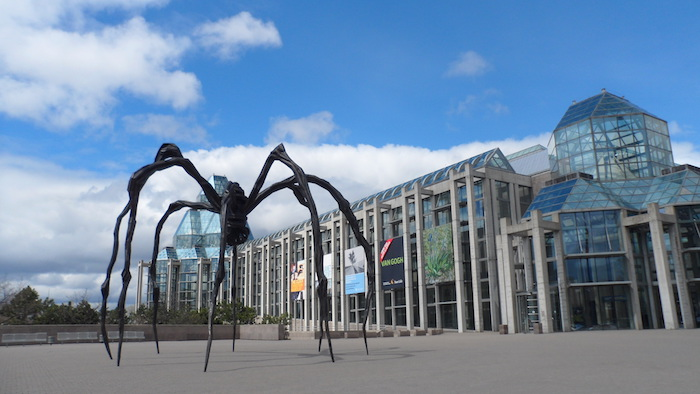 sculpture of a giant black spider, near a building, made of concrete and glass, supported by off-white columns, postmodernism examples, canadian national gallery